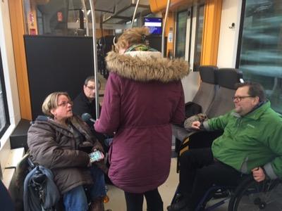 Bild im inneren des Zugs. Gracia Schade spricht in ein Mikrofon,mdass die mitreisende SWR Reporterin  hält