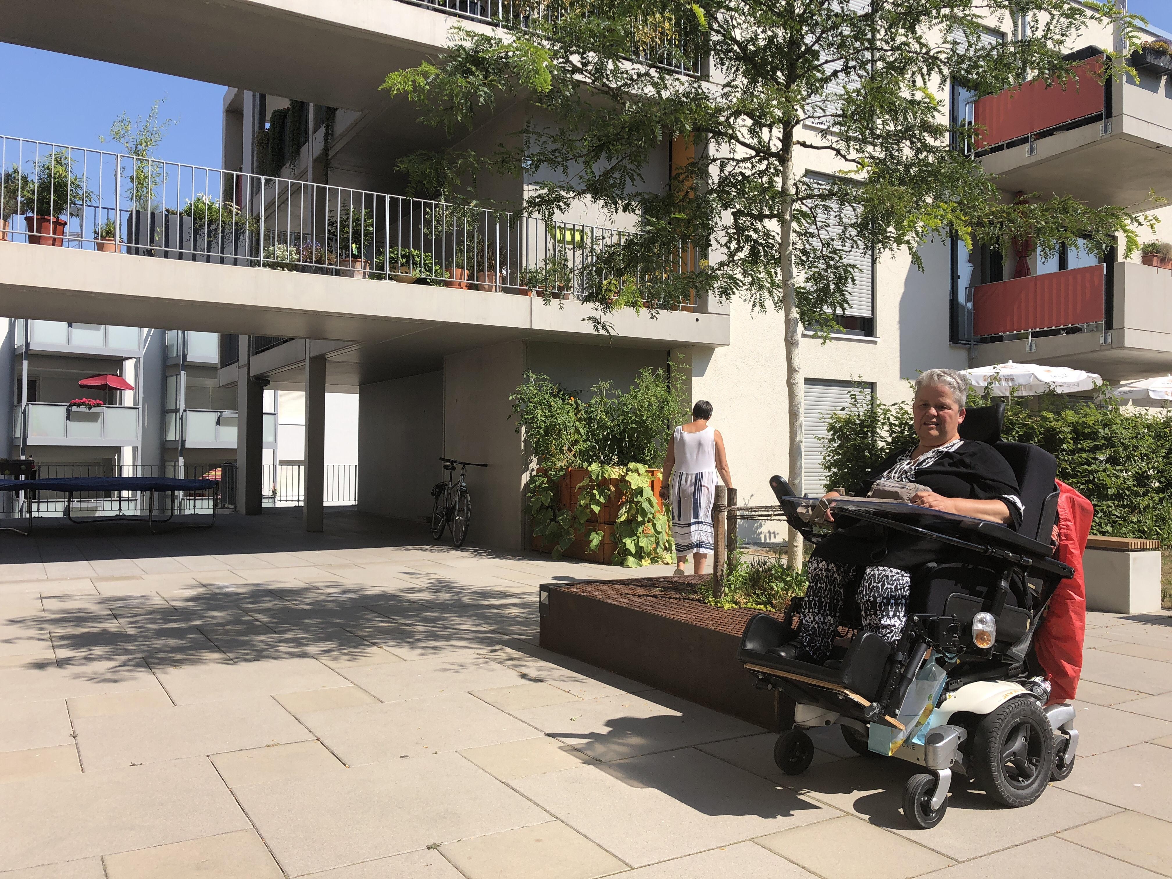 Bewohnerin mit Rollstuhl mit. Außenansicht des Gebäudes