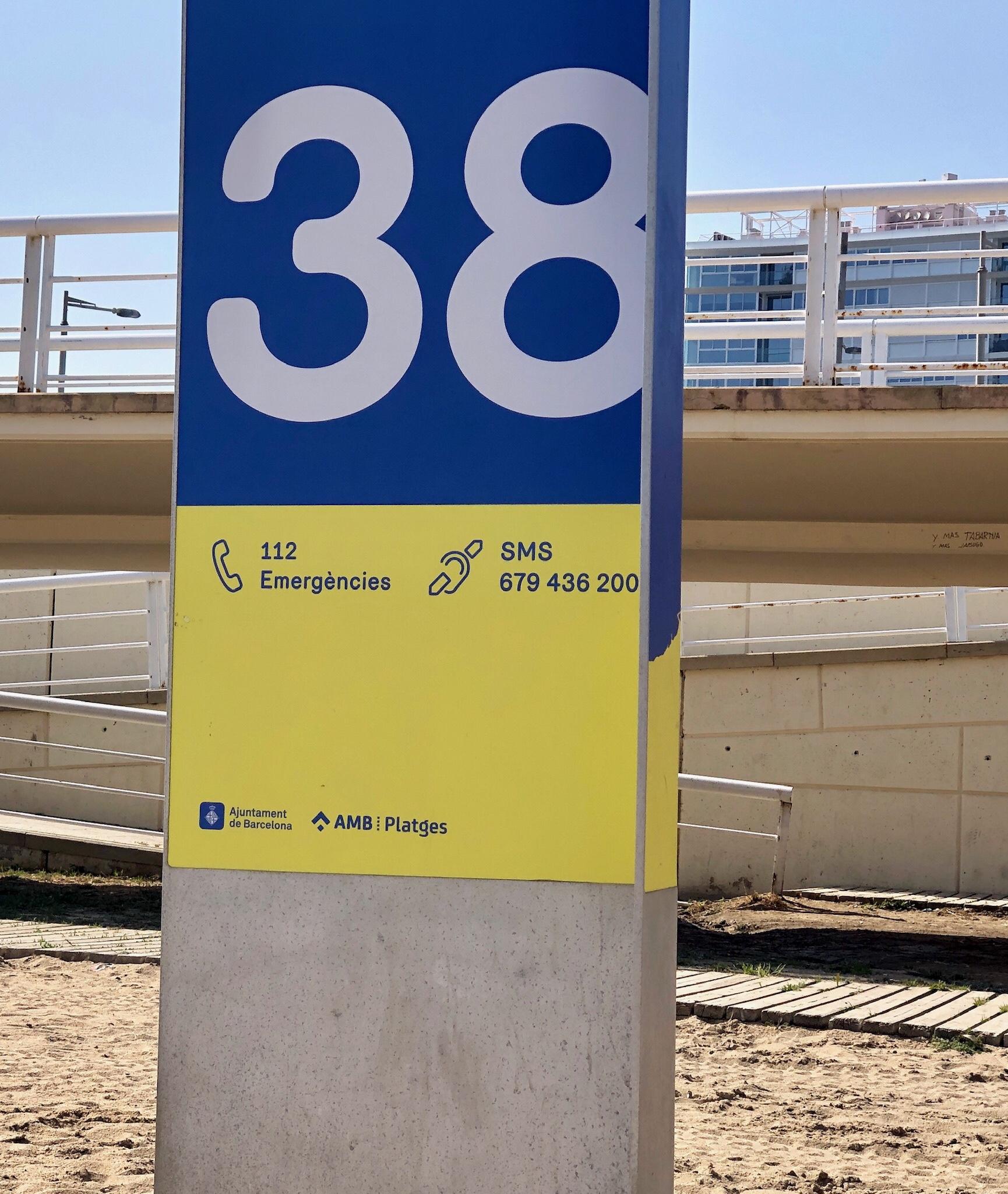 Hinweisstele am Strand von Barcelona mit Hinweis auf Notrufnummern