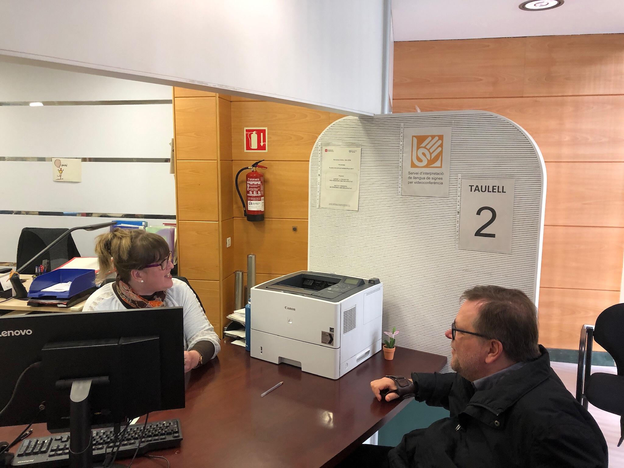 Mitarbeiterin des Bürgerbüros am Schreibtisch erklärt den Service